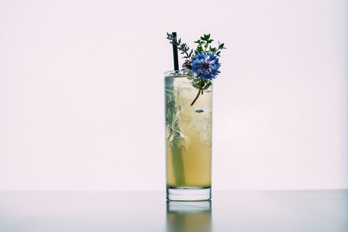A summery cocktail garnished with edible flowers from Roof 106