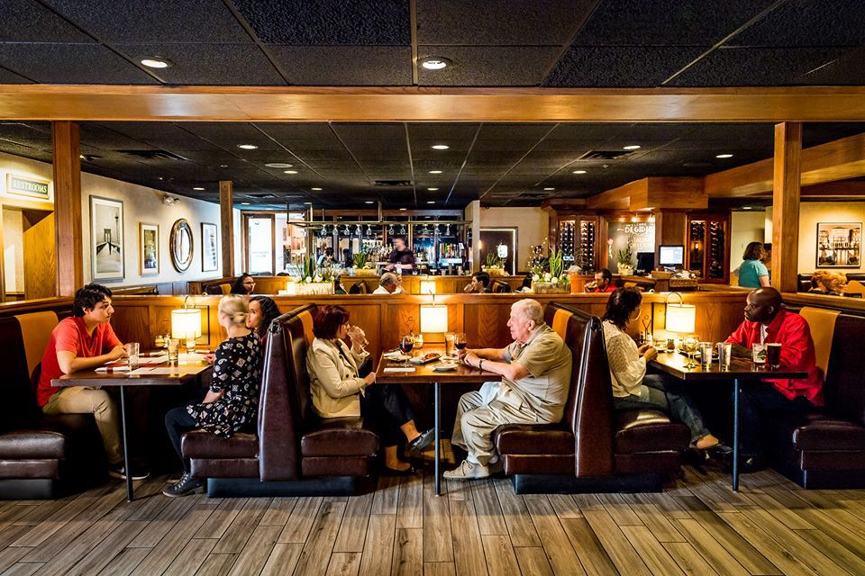 A cozy dining room with booths filled with people. This photo was taken last year.
