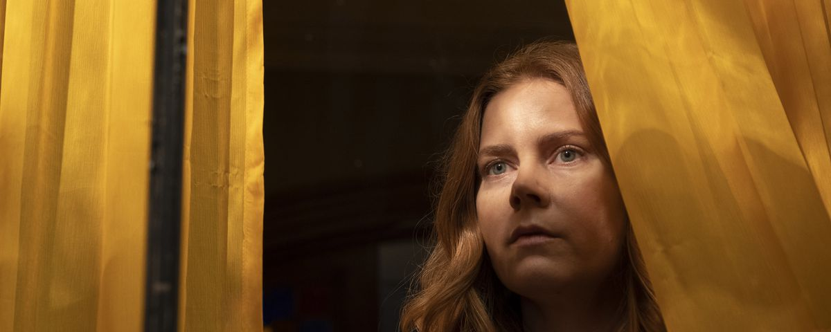 Amy Adams in The Woman in the Window, appropriately standing in a yellow-curtained window