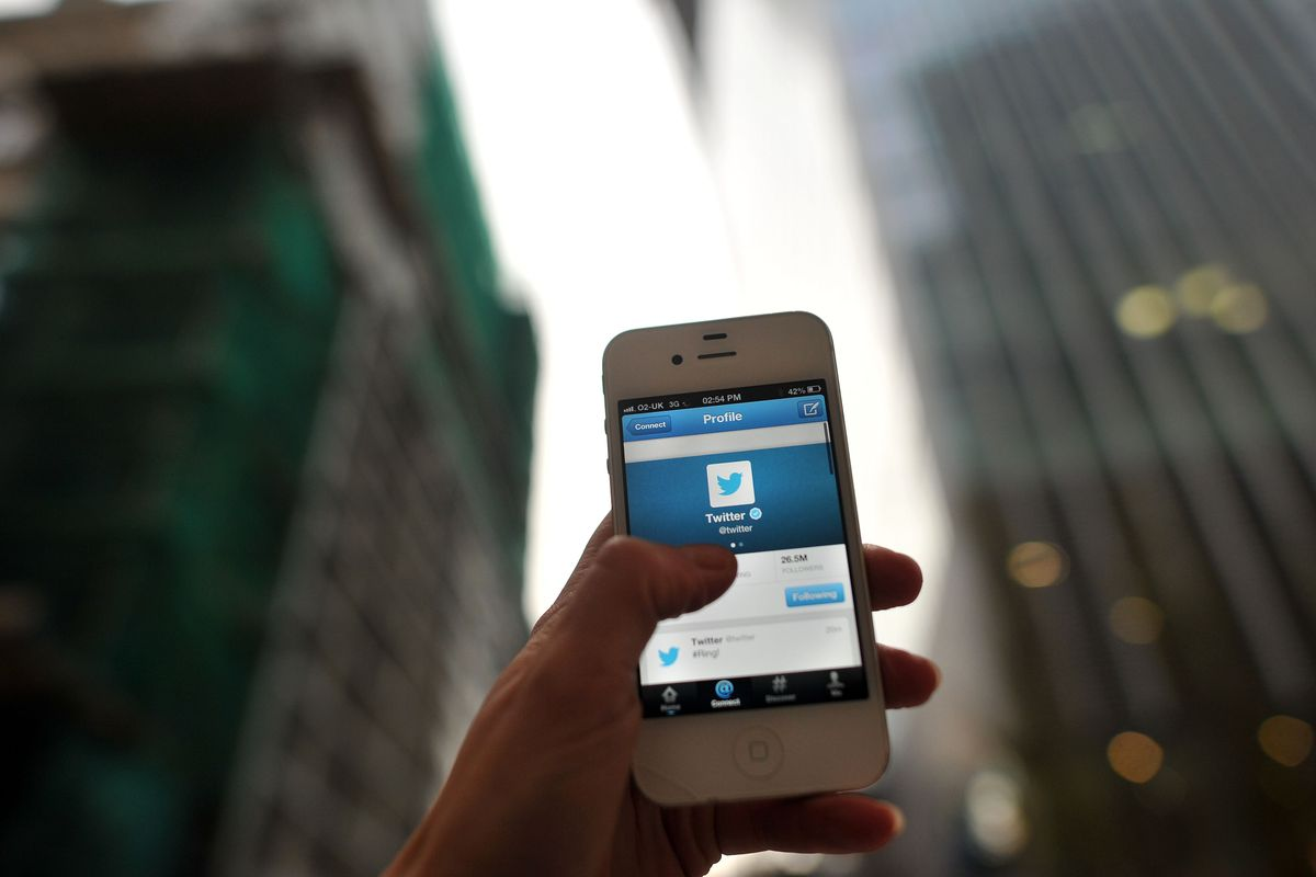 A hand holding a mobile phone displaying a Twitter page. There are New York buildings in the background.