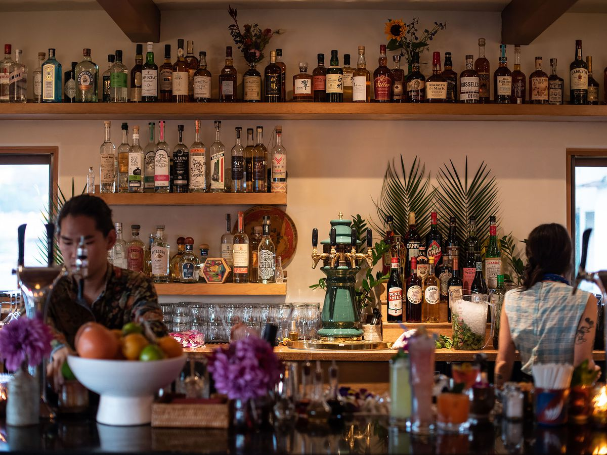 Bartenders behind the bar at Bar Flores in Echo Park with colorful bottles on the wall.