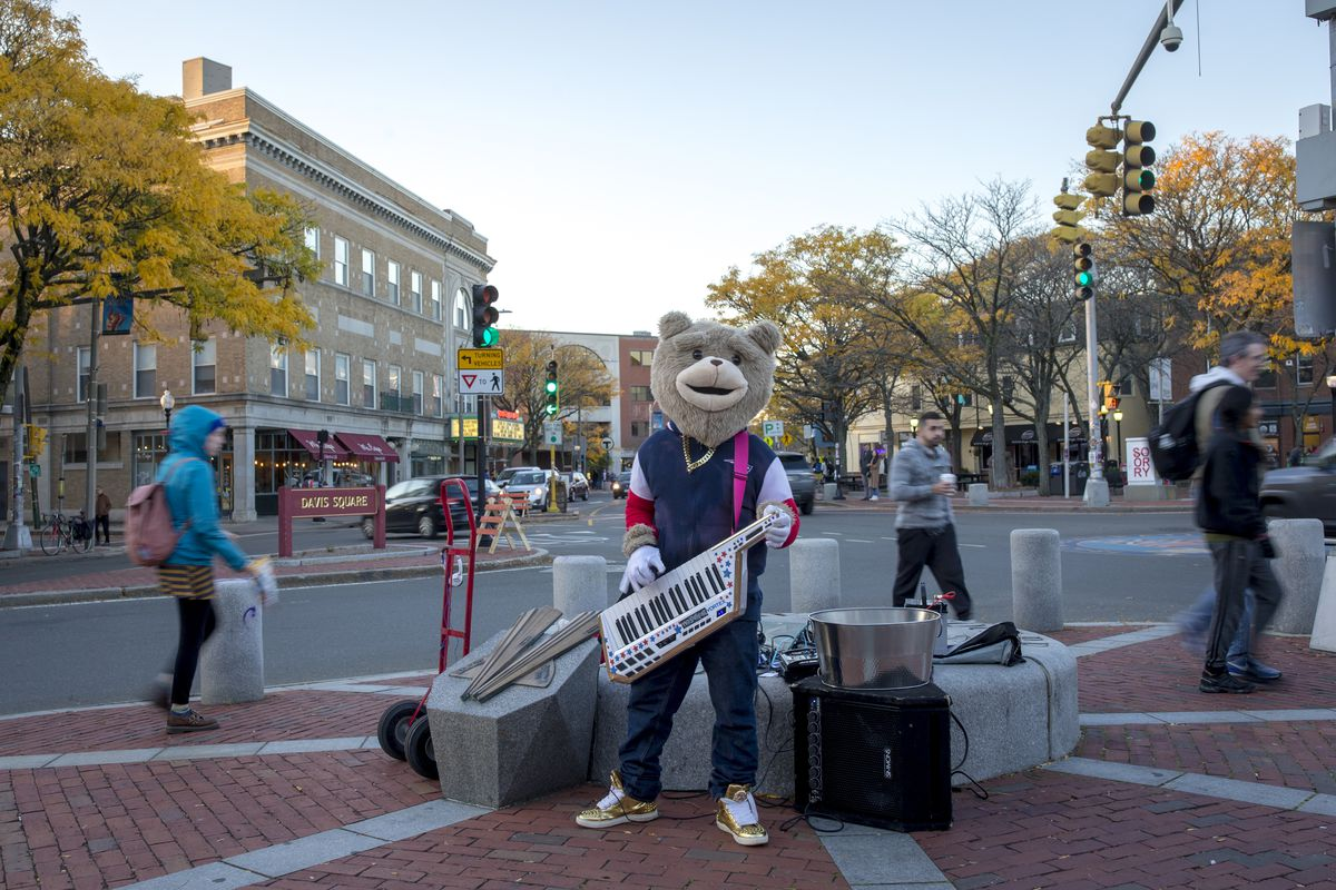 A man dressed as a bear playing a keyboard guitar in a busy urban area.