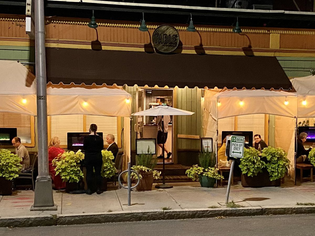 Outdoor dining setups in Cambridge, in the form of cabanas. A server greets a table, which is also under an awning.