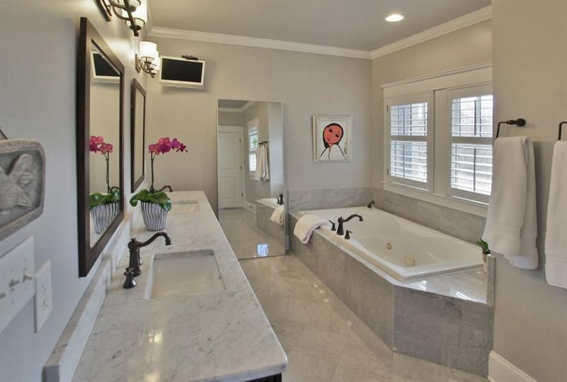 A large master bathroom with marble all around it.