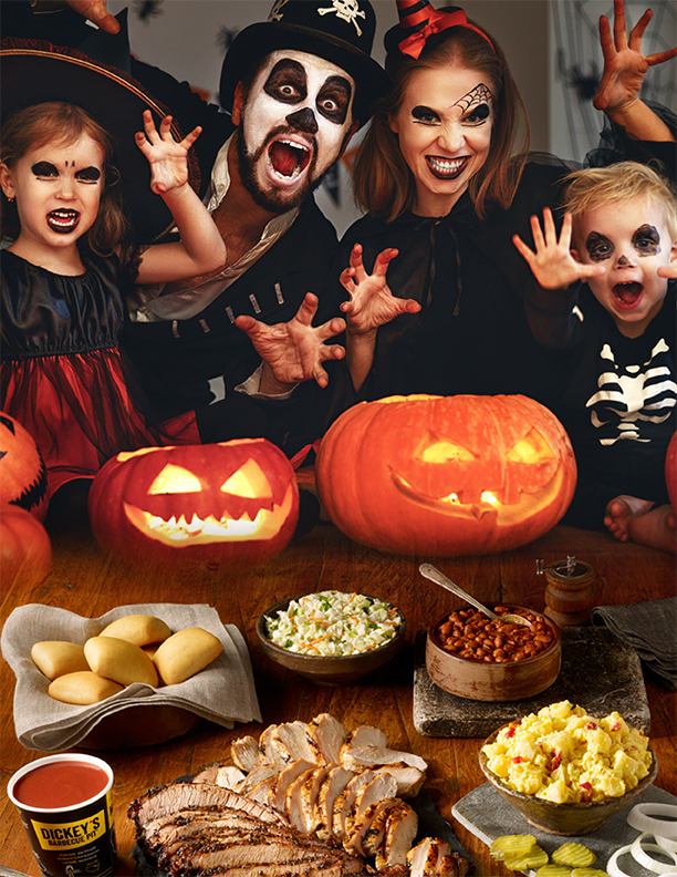 Children and adults wear costumes wiith two pumpkins in front of them.