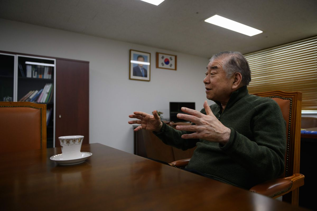 Moon Chung-in speaks with his arms raised at his office in Seoul.