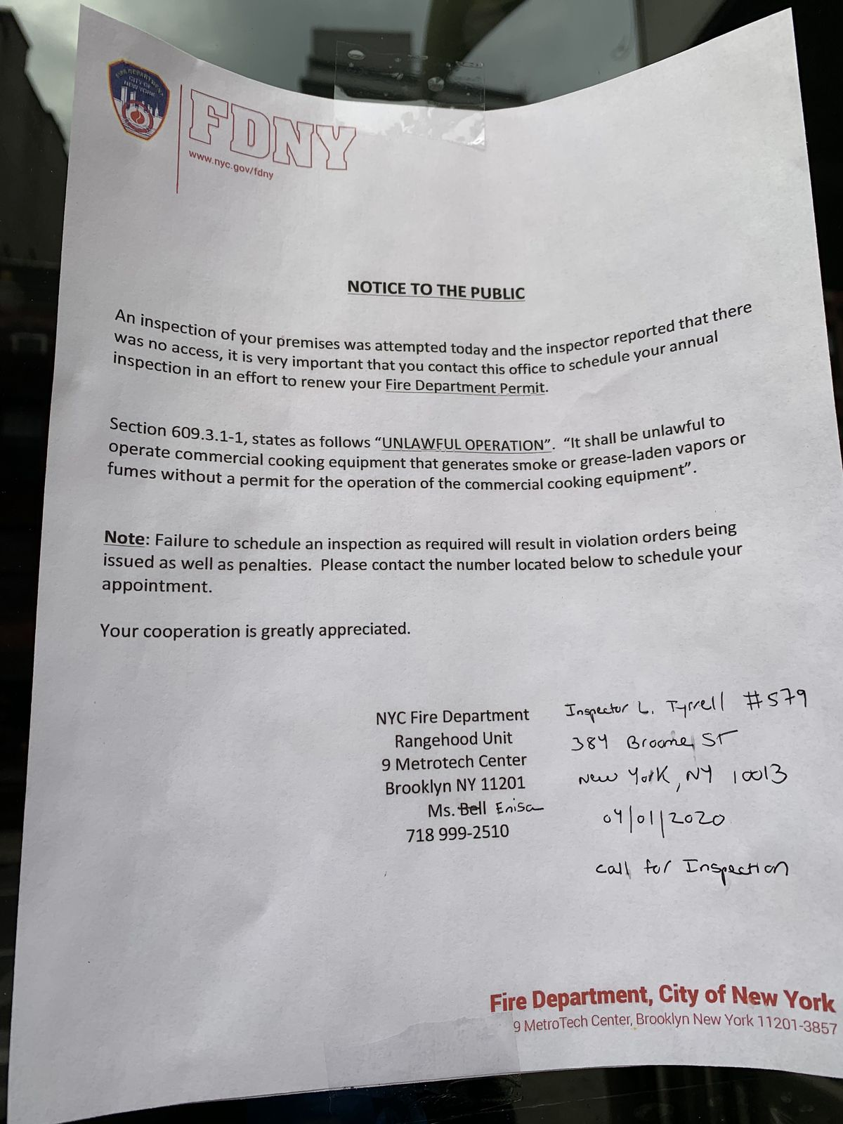 A notice from the FDNY taped on a restaurant's front door stating that an inspection of the premises wasn't allowed to be completed