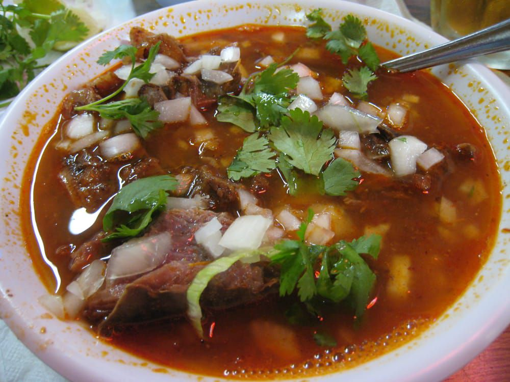 El Parian's bowl of goat birria served in a deep red sauce.