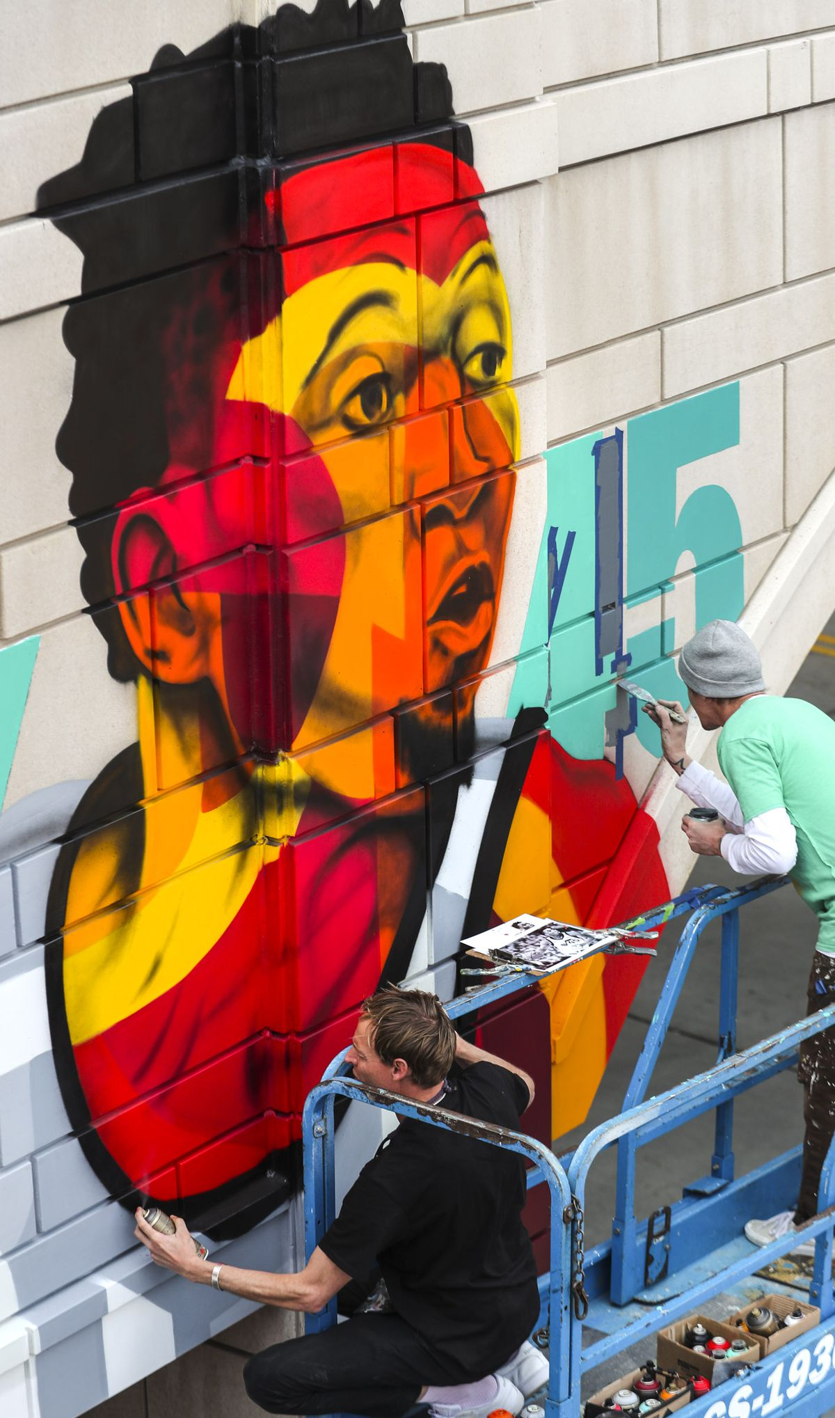 Artists Chuck Landvatter and Jared Smith work on a painting of Donovan Mitchell, of the Utah Jazz, prior to an event where the pedestrian bridge spanning 100 South at The Gateway in Salt Lake City was named after Mitchell on Tuesday, March 26, 2019.