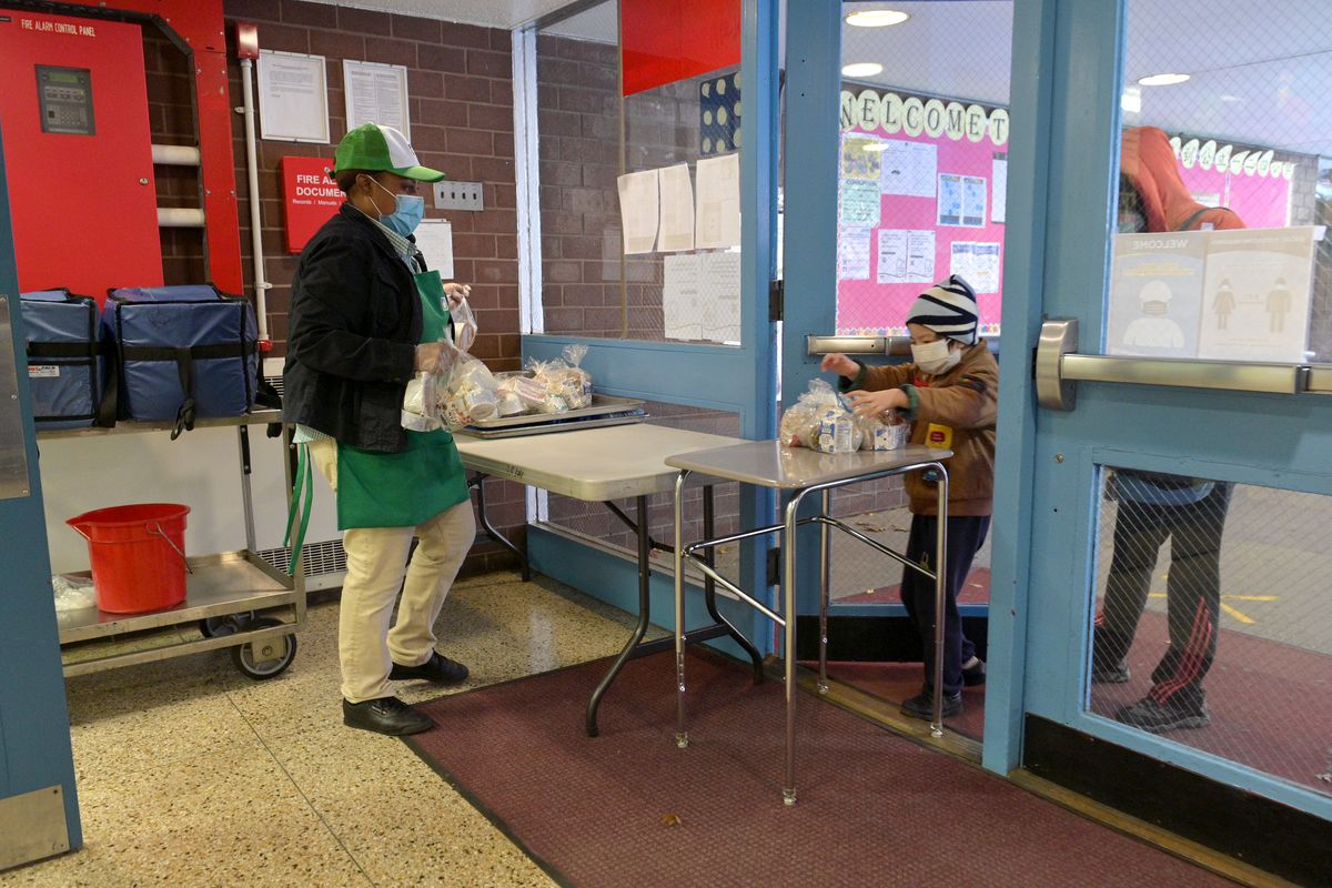 Cafeteria worker wearing mask watches child pick up meal from a table.