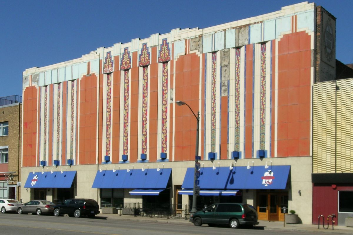 Facade of a several-story Art Deco building with orange paint and vertical strikes of blue and white. There's also a blue awning over the ground-floor windows.