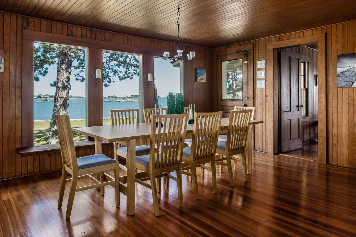A dining room can seat eight on wood floors with three large windows that look out to green grass and blue water.