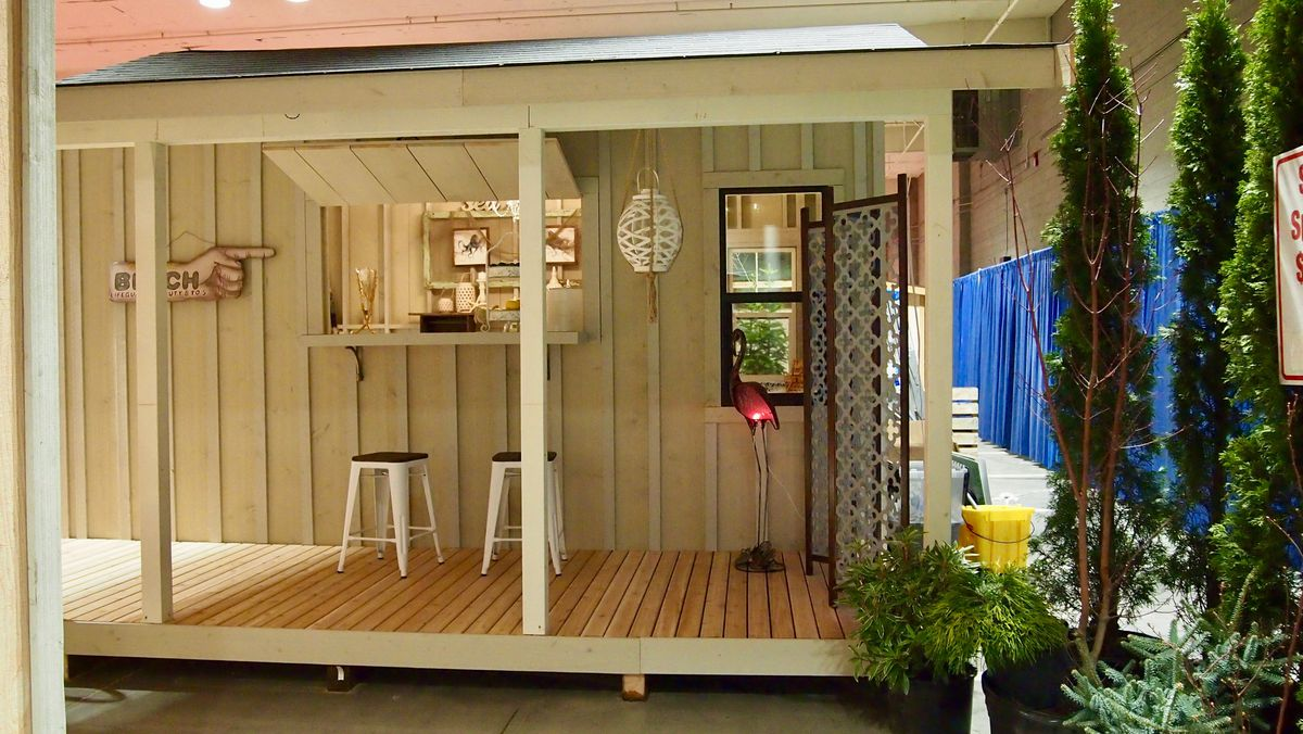 The side of a shed features a window that opens up into a counter with stools.