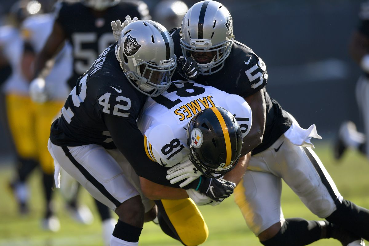 The Pittsburgh Steelers' Jesse James gets tackled by Oakland Raiders players Karl Joseph and Tahir Whitehead