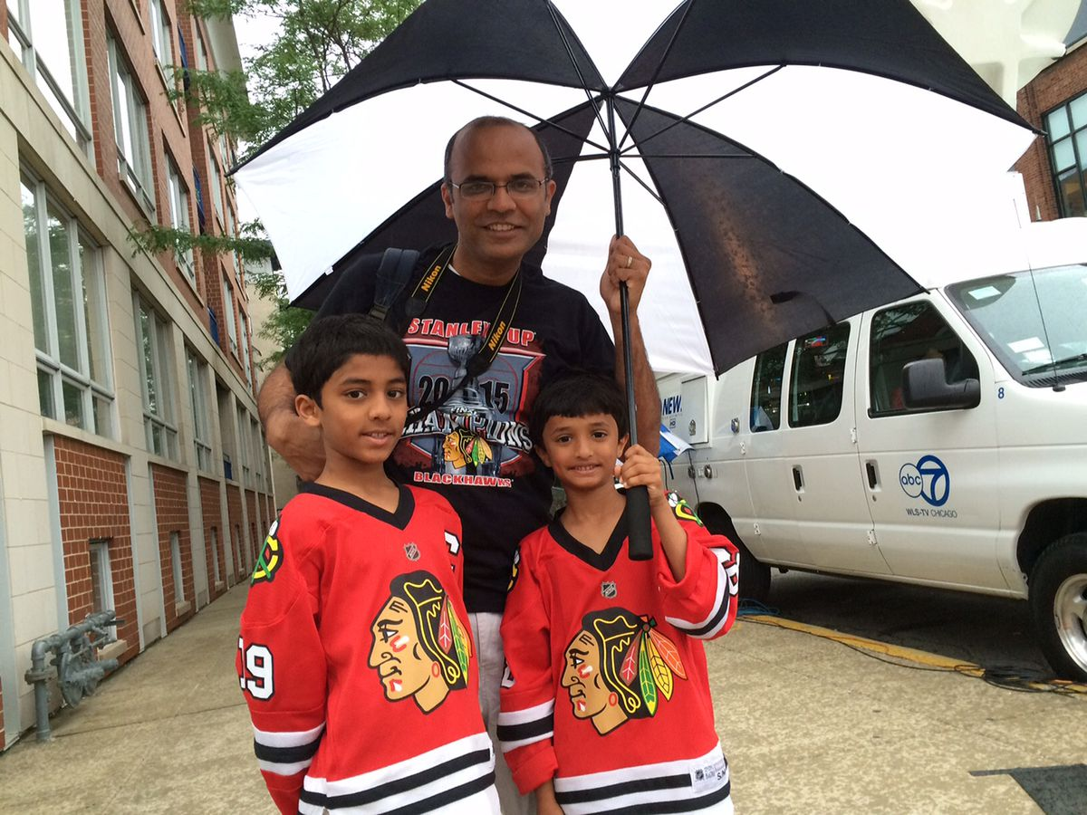 Mehul Patel, 39, and his children Kunal, 7, and Kushal, 9, all of Elgin, try to stay dry near the start of the parade route. | Stefano Esposito/Sun-Times