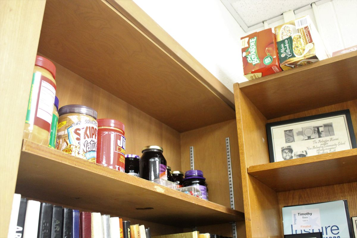 Supplies for the alumni snack pantry line a bookshelf at Arlington High School. Alumni donate money and food to the pantry, so students staying after school can have something to eat.