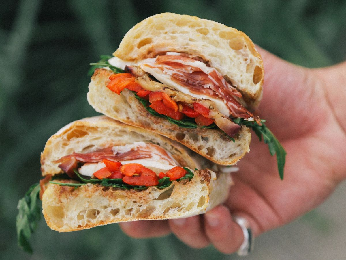 Italian sandwich with meats and arugula being held by hand.