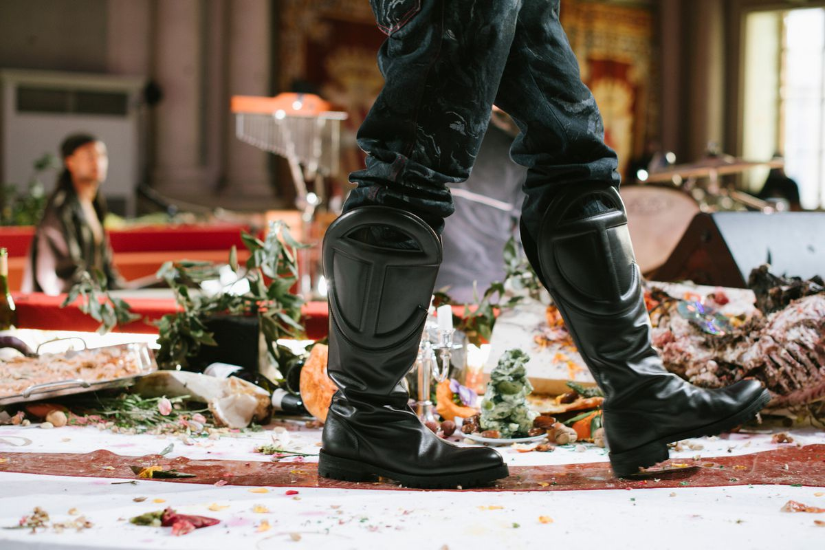 Person with large black boots and pants walks atop a table.