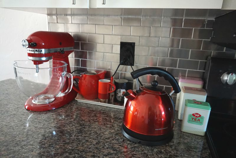 Kitchen counter top featuring red kitchen mixer, kettle, mug, and rectangular tins containing tea,