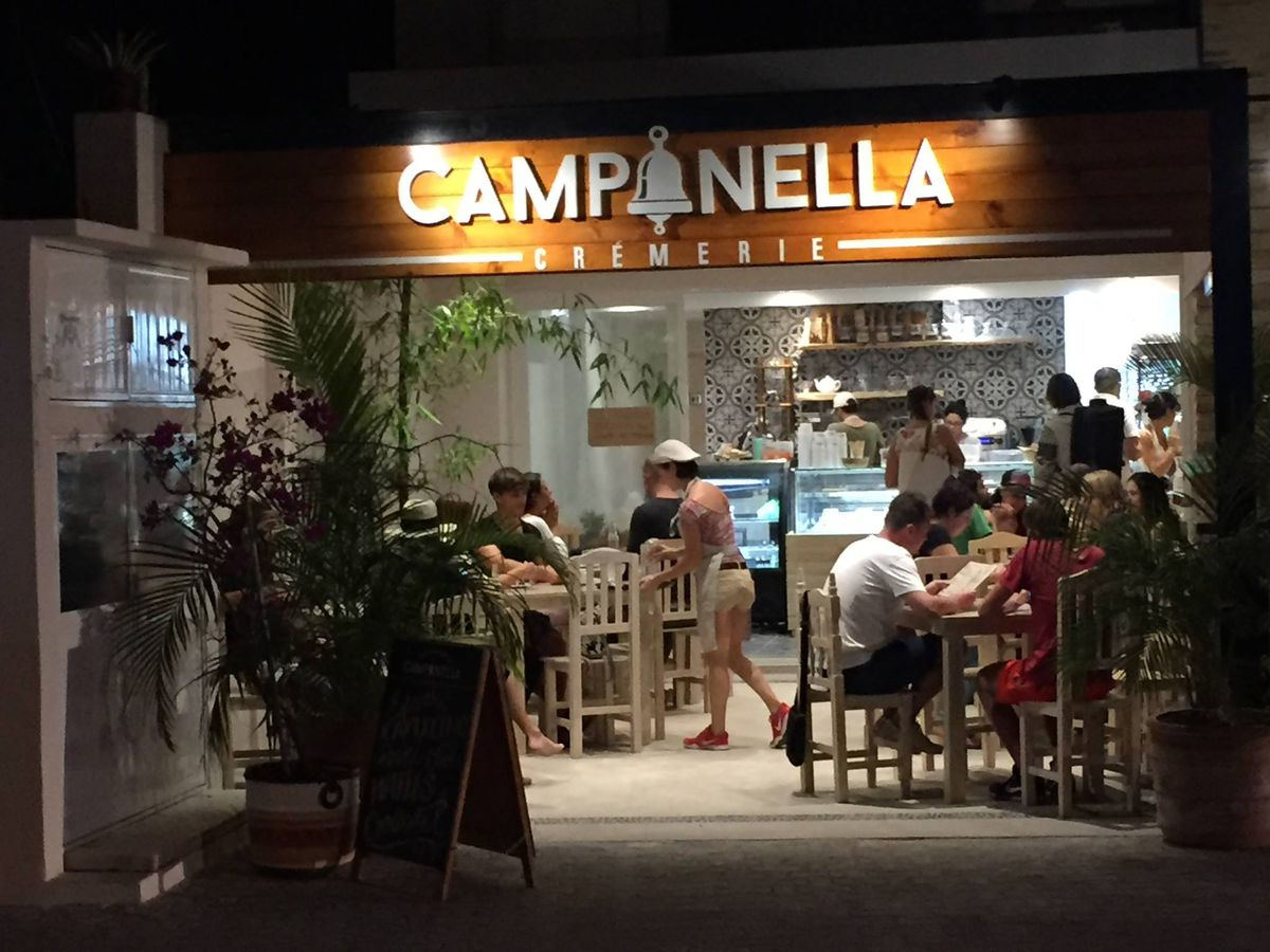 At night, diners sit at outdoor tables in front of the lit-up Campanella Cremerie sign, which is displayed above the interior of the gelateria where an ice cream counter is visible and servers move about.