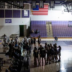 Players, coaches and staff wait on the court after power went out at the start of the girls basketball game between Riverton and Syracuse at Riverton High School on Tuesday, Dec. 15, 2020.