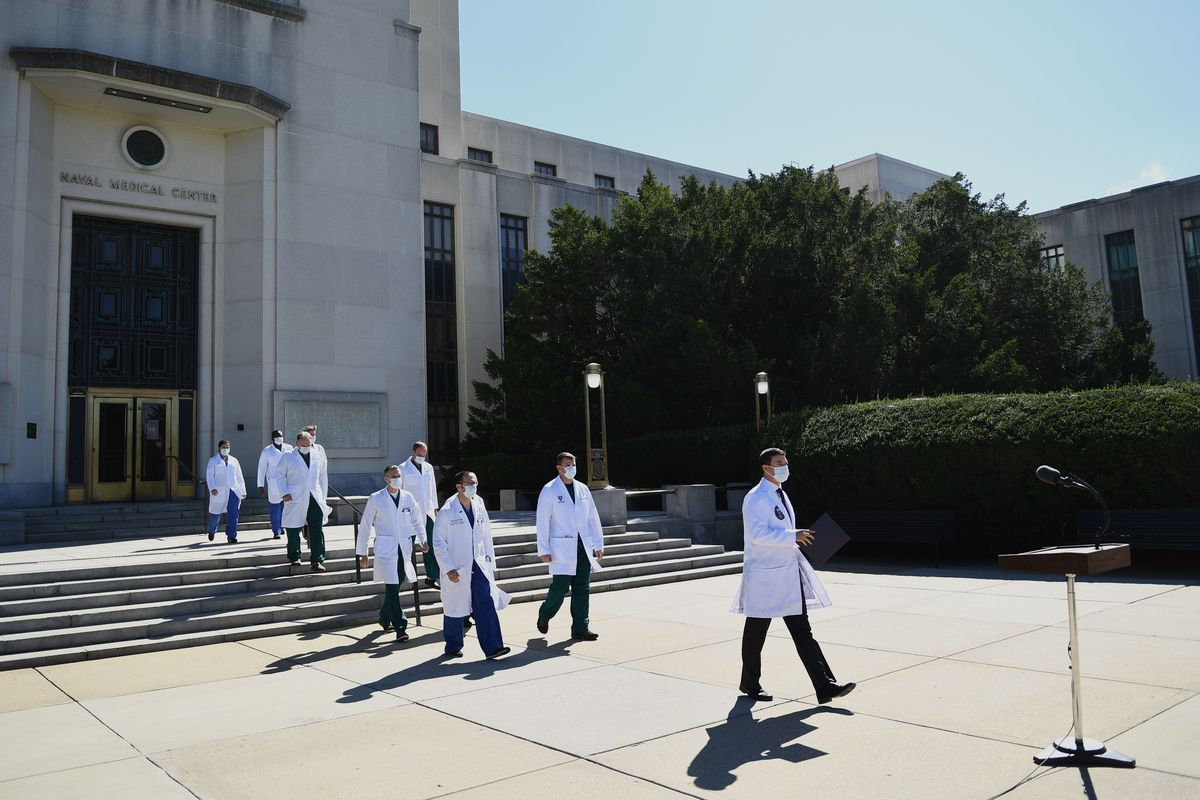 Nine figures in white coats walk down the stone steps of Walter Reed towards a microphone. They cast long shadows, the sun to their lefts. Behind them, the pale stone of the medical center looms tall above them.