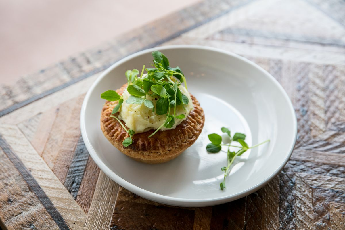 The Aussie meat pie from folk is shown on a plate with mashed potatoes on top and pea shoots.
