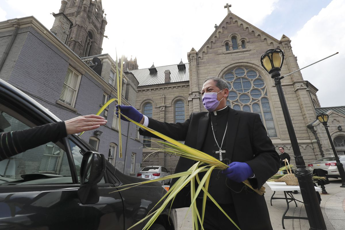 Bishop Oscar Solis hands out a palm at the Cathedral of the Madeleine in Salt Lake City on Sunday, April 5, 2020.