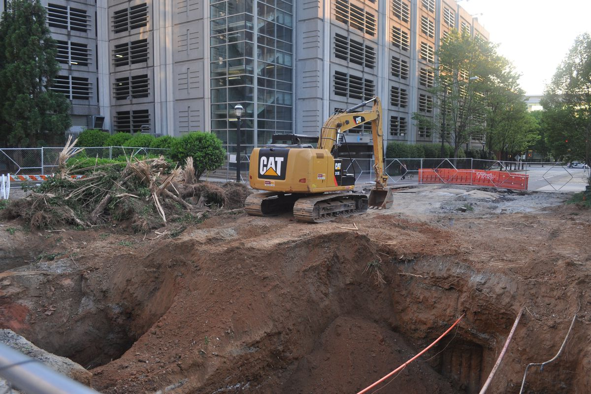 A massive pit stretching across 5th Street, with a backhoe and uprooted plants.