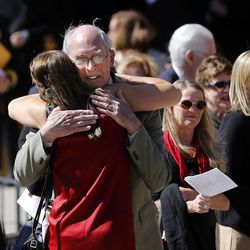 People hug following the memorial service for Deedee Corradini at Wasatch Presbyterian Church in Salt Lake City, Monday, March 9, 2015.
