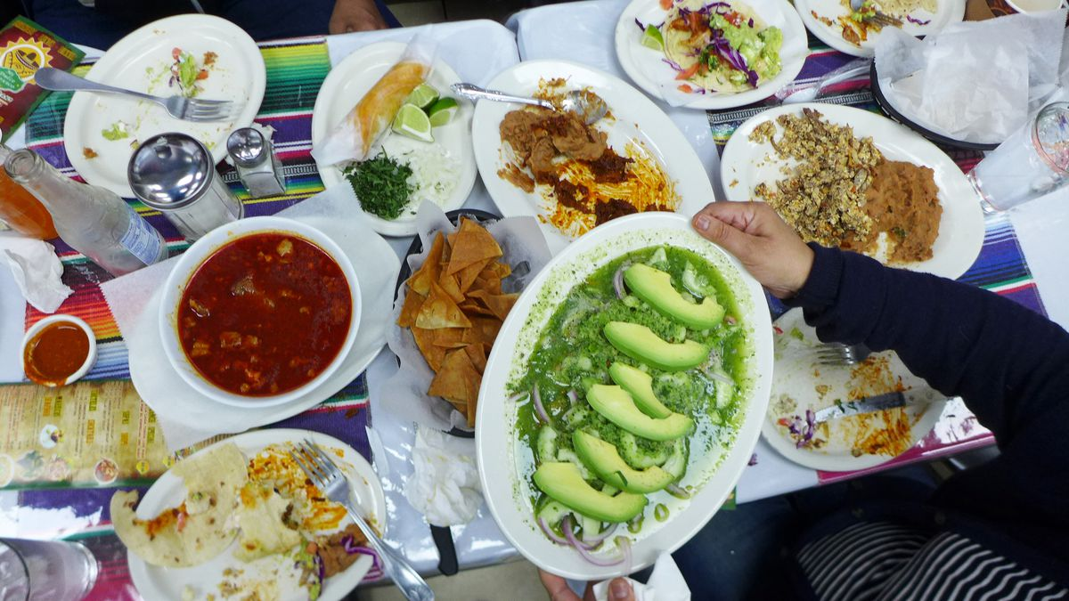 Many plates skewed on a long table, a plate of green shrimp aguachile foremost and held aloft.