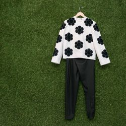 Steven Tai long sleeve top with fuzzy embroidery, $498; House of 950 fold-over pants, $250