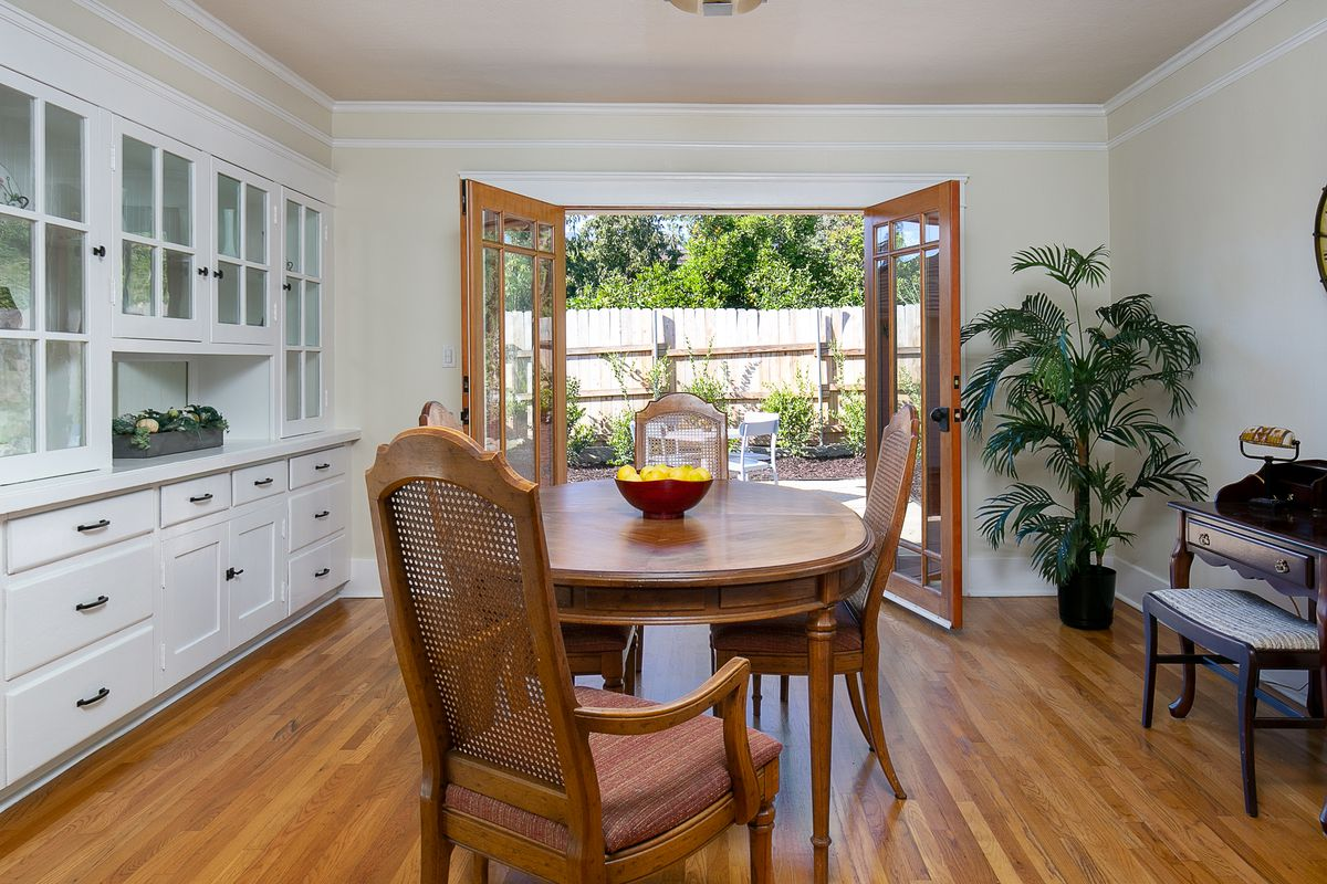 A room with a circular dining room table and chairs