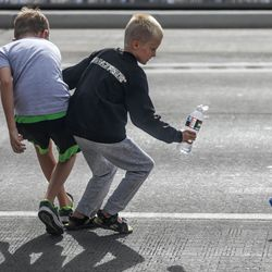Children dive for a free shirt thrown during the Grand Parade in Provo on Monday, July 5, 2021.