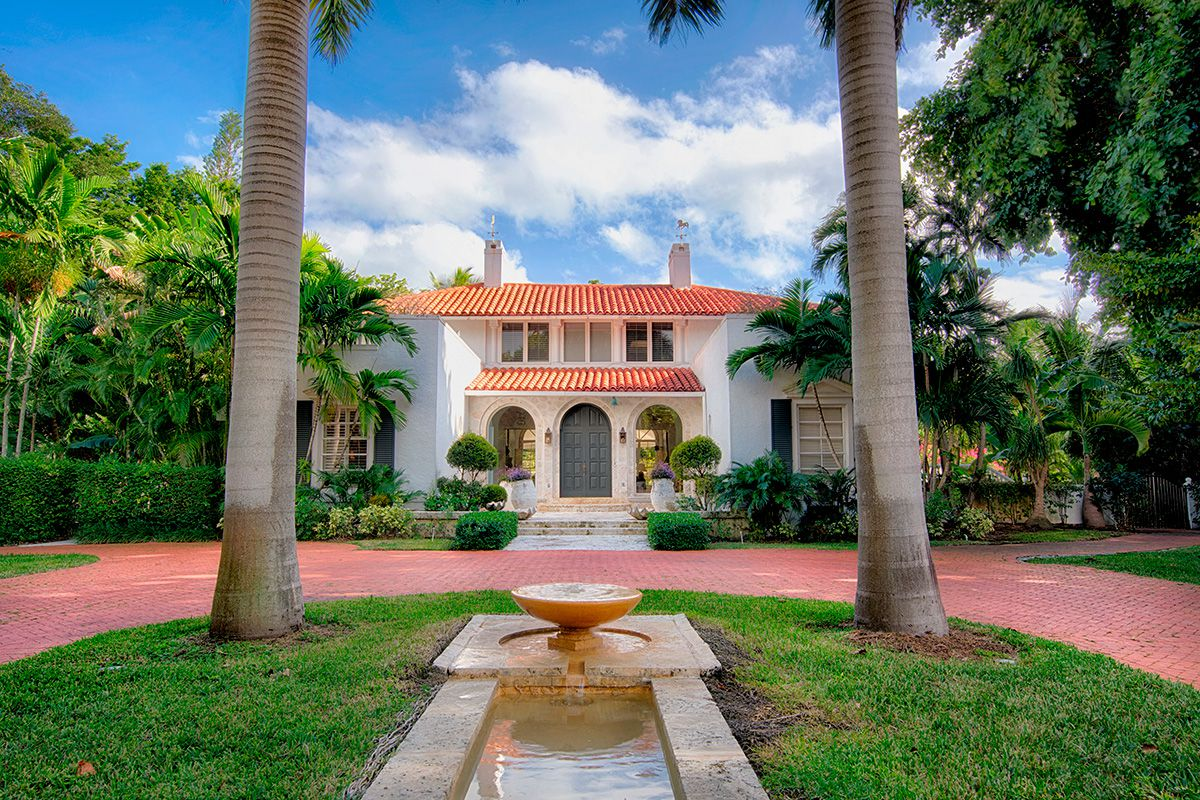 Outdoor view of a historical home in Coral Gables, a classical revival home with arched entry, an orange roof, and two large palm trees out front.