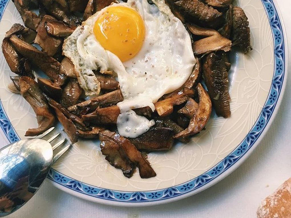 A plate covered in mushrooms, topped with a fried egg.