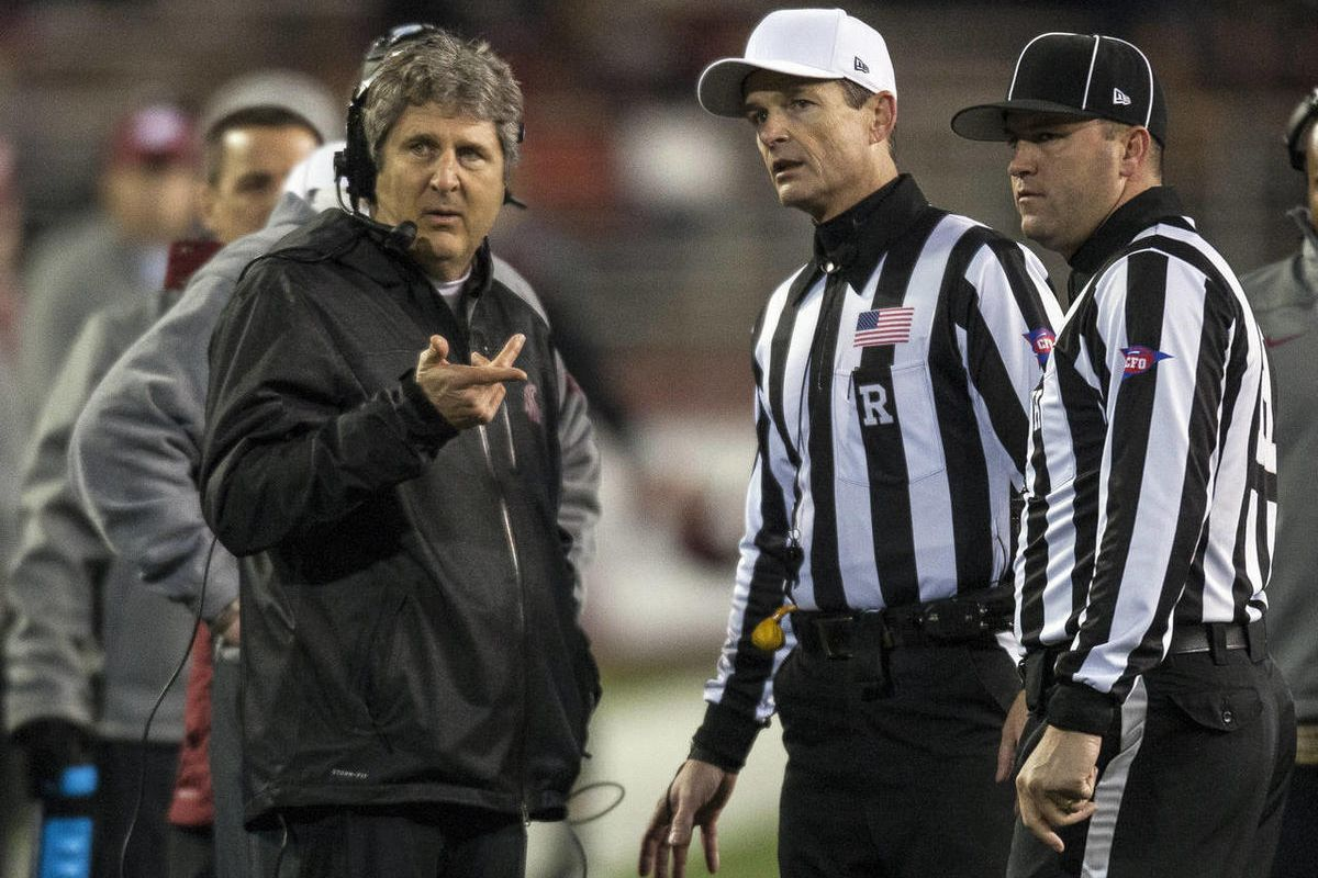Washington State head coach Mike Leach, left, asks referee Land Clark, center, and head linesman Bart Longson, right, a question during the first half of an NCAA college football game against Arizona State, Thursday, Oct. 31, 2013, at Martin Stadium in Pu