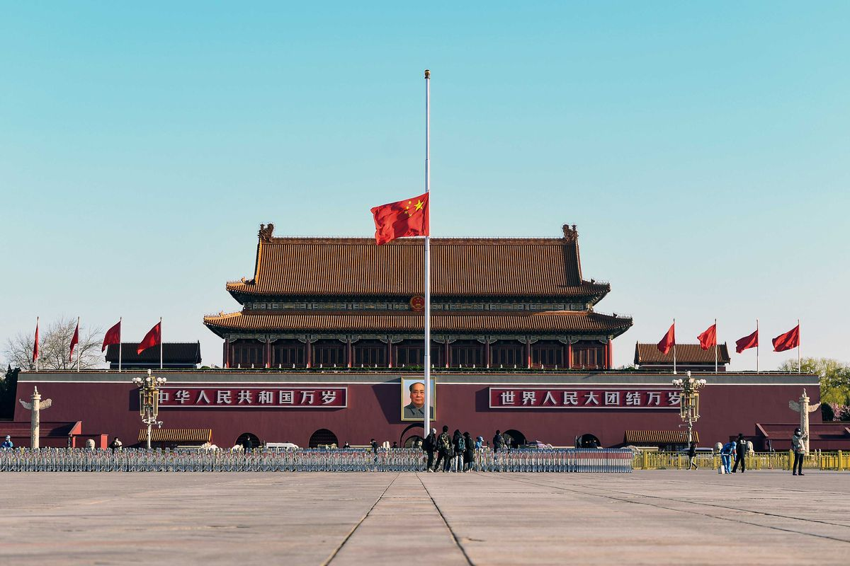 The Chinese flag flies at half staff in front of the peaked-roofs of Tiananmen Square.