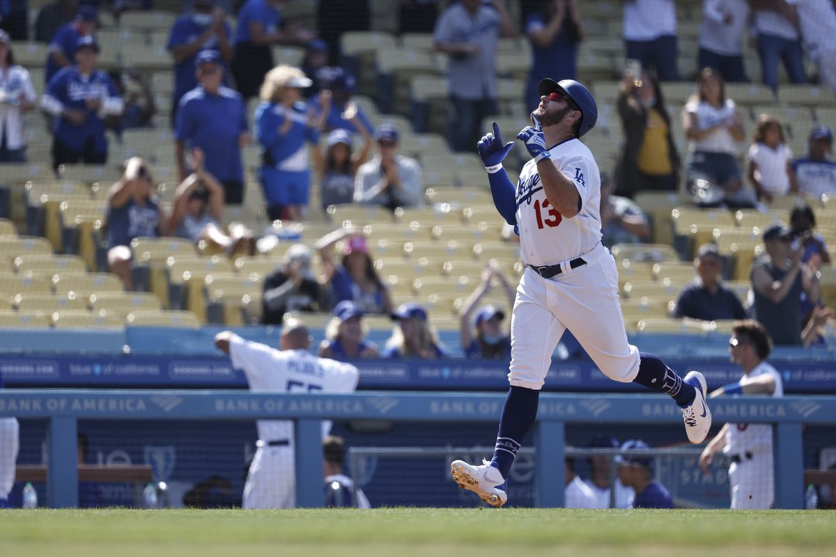 Max Muncy #13 of the Los Angeles Dodgers celebrates as he runs home after hitting a two-run home run against the San Francisco Giants during the eighth inning at Dodger Stadium on May 30, 2021 in Los Angeles, California. Austin Barnes scored.