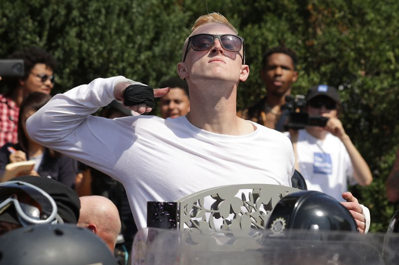 A man makes a slashing motion across his throat twoard counter-protesters as he marches with other white nationalists, neo-Nazis and members of the 'alt-right' during the 'Unite the Right' rally August 12, 2017 in Charlottesville, Virginia.