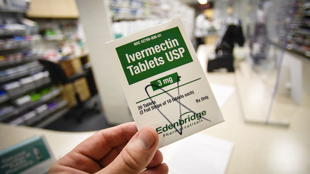 A hand holding a small packet labeled Ivermectin Tablets USP. In the background is the aisle of a drugstore.