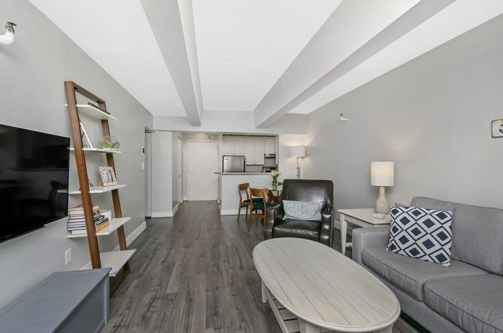 A long, low-ceilinged, open living room with a couch.