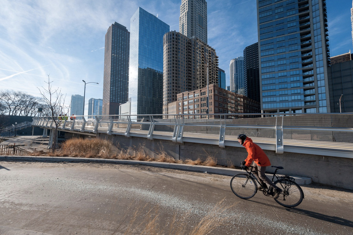 A man in a red jacket on a bike rolls on an asphalt path with tall, glassy city buildings in the background.