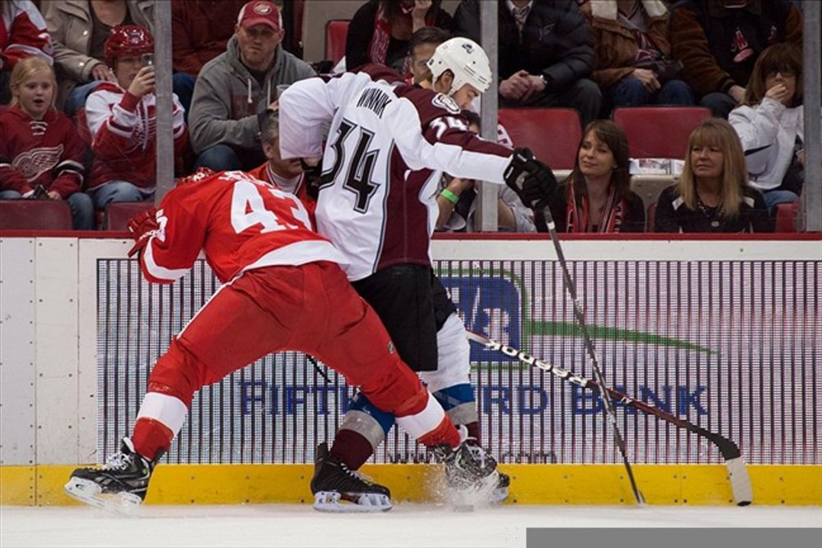 Feb 25, 2012; Detroit, MI, USA; Detroit Red Wings center Darren Helm (43) and Colorado Avalanche left wing Daniel Winnik (34) battle for the puck during the first period at the Joe Louis Arena. Mandatory Credit: Tim Fuller-US PRESSWIRE