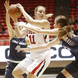 Utah's Taryn Wicijowski, center, passes the ball away as she is defended by Utah State's Devyn Christensen, left, and teammate Cristal Turner as Utah and Utah State play , in the Huntsman Center. Utah won 92-64.