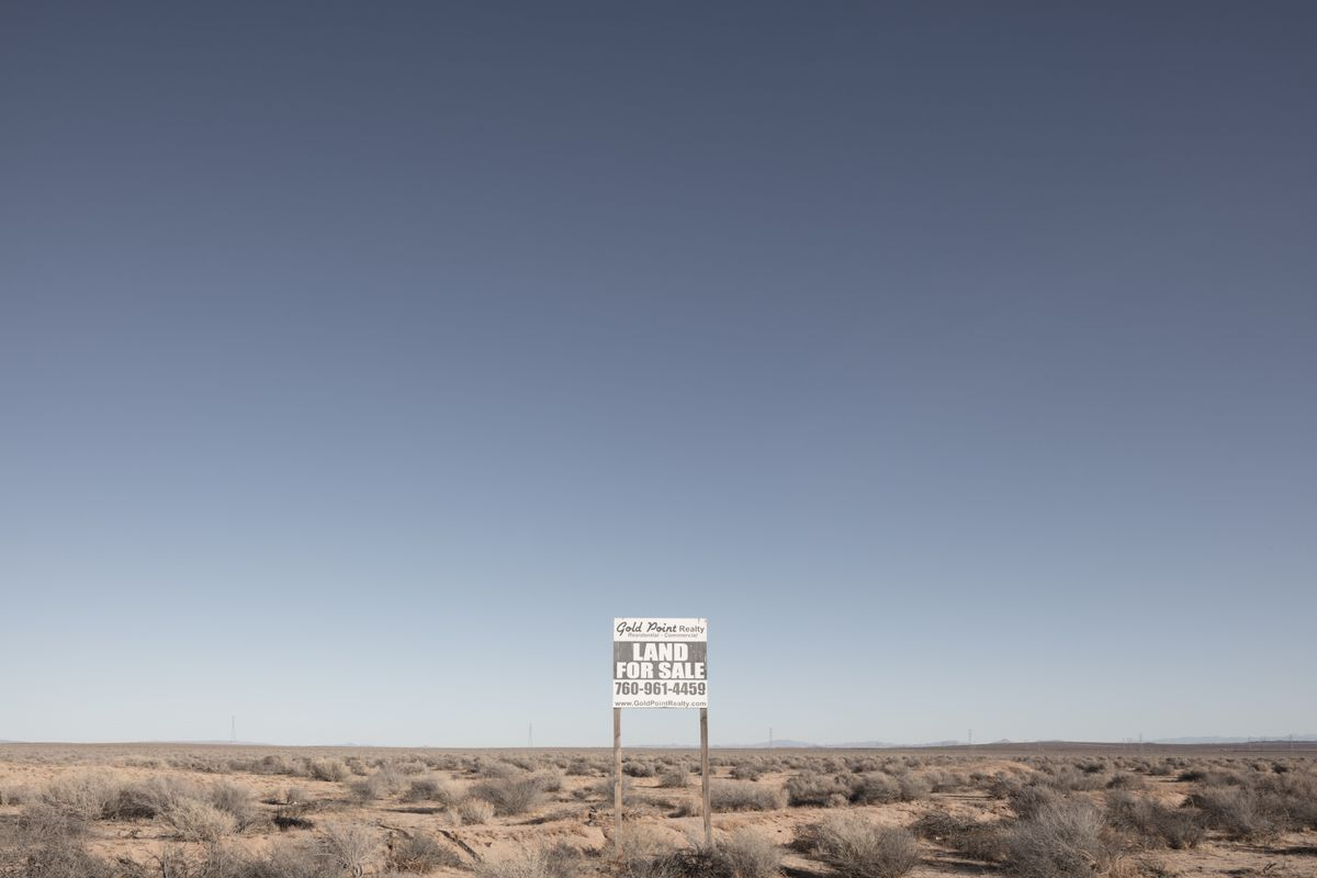 The California desert with a sign that reads: Land for sale.