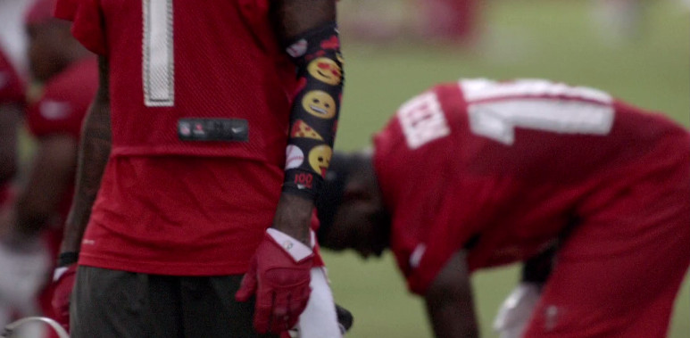 DeSean Jackson's arm covered in a black sleeve with emoji on it