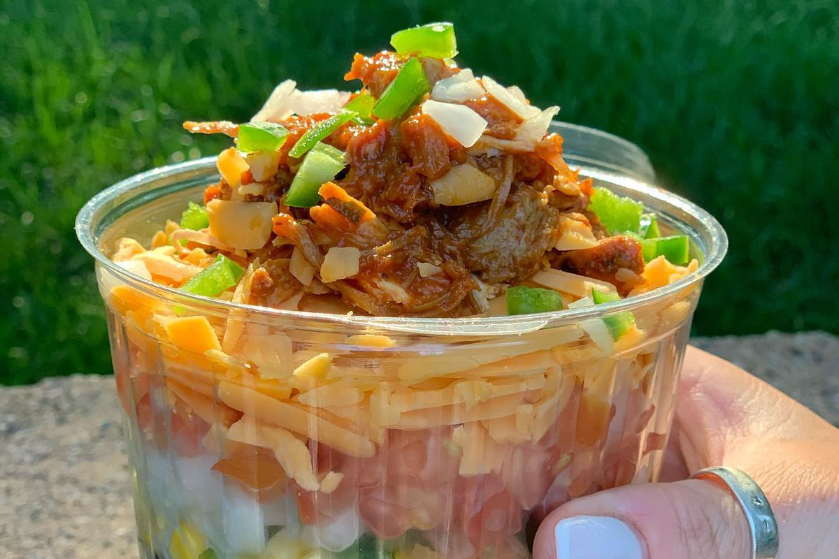 a bowl with layers of corn, shredded cheese, tomatoes, onions and pulled pork
