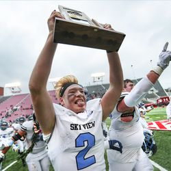 Sky View quarterback Kason Carlsen races to the student body section as he holds the 4A championship trophy over his head after the Bobcats defeated Park City at Rice-Eccles Stadium in Salt Lake City on Friday, Nov. 22, 2019.