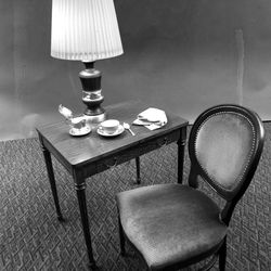 """Hotel Utah Empire Room chairs such as this will be auctioned in sets of four. Writing desk and lamp are among more contemporary furniture in the auction. A single place setting of the pink, white and gold china will also be auctioned, along with the silver creamer. """"The Roof"""" napkins will be offered for sale. March 1988."""